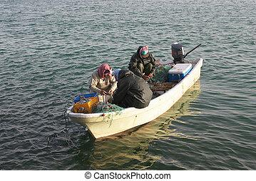 Landing the catch - Three Asian fishermen land their catch...