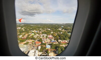 Landings at the airport Tagbilaran. Low flight over the city. Electronic video stabilization. View from the airplane window.
