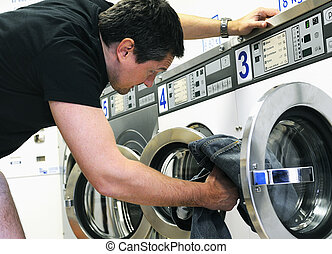 landromat service - man is using washing machines in a ...