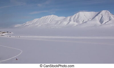 Landscape and buildings, roads in Small town Longyearbyen on shores of Arctic ocean among snow capped mountains of Norwegian Archipelago of Svalbard in early spring in Norway. Sunny day in April.