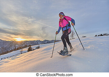 Landscape at sunset in the mountains with girl running downhill with snowshoes