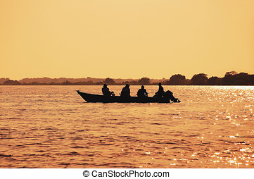 Landscape at sunset of a boat with fishermen fishing on Pantanal