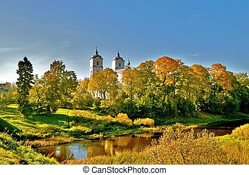 Autumn landscape in Lithuania with church, river and tree