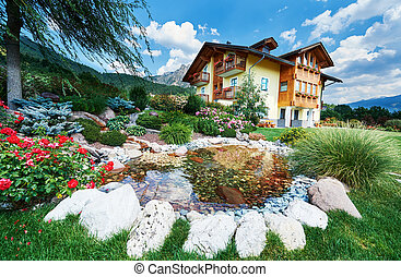 Landscape design. Decorated pond and flowerbed with alpine house