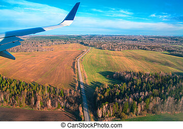 Landscape fields surrounded by forests from the window aircraft. View of farmland from a bird's-eye view. Top view.