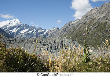 Landscape shingle mound between mountain ranges leading to Mount Cook, from highway through Southern Alps In South Island New Zealand