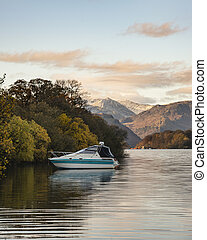 Landscape image of boat moored on Ullswater in Lake District with snowcapped mountains in background with beautiful vibrant Autumn Fall colors