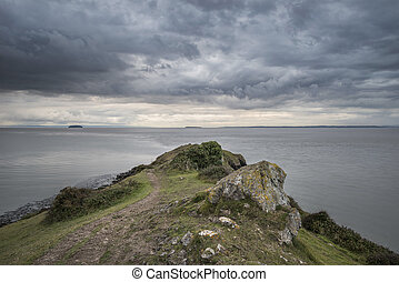 Landscape image of view out to sea with storm cloud sky overhead