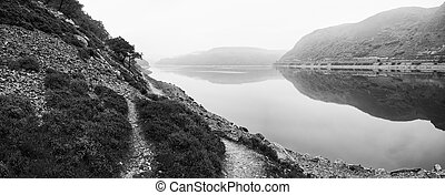 Landscape image over misty lake in Autumn Fall in monochrome