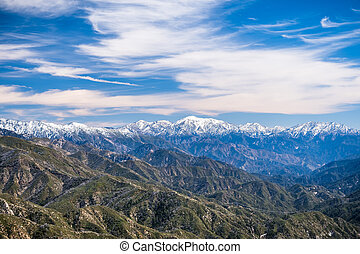 Landscape in Angeles National Forest on a sunny day; mountains covered in snow in the background; Los Angeles county, south California