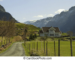 landscape in norway with house in deep valley. fence and green hayfield in foreground