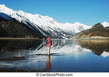 Snow Mountains and their mirror in a lake, Tibet, in a Spring morning