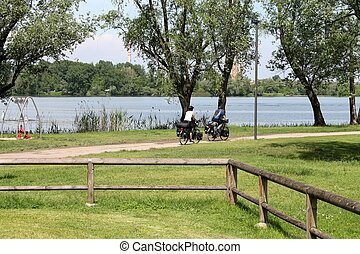 landscape lake with people in bicycle