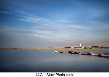Landscape long exposure of lighthouse and jetty during Summer su