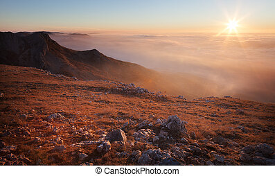 Mountain slopes in the mist at sunrise