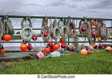 Landscape of a harbor with fisherman's equipment with orange buoy, rope and nets hanging over a gate