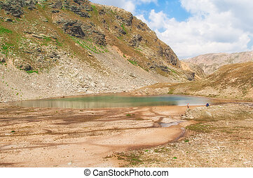 landscape of an alpine lake with cloudy sky