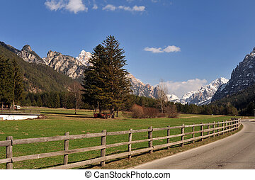 Landscape of Dolomites mountains in summer with a farm and meadows near a fence