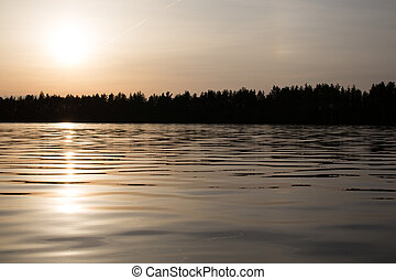 Landscape of forest and lake in the evening.