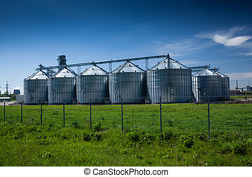 grain elevator at field against deep blue sky