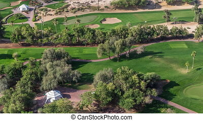 Landscape of green golf course with trees aerial timelapse....