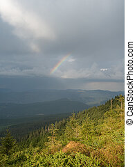 Landscape of hillsides after rain. Low dark clouds and...