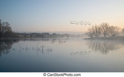 Landscape of lake in mist with sun glow at sunrise