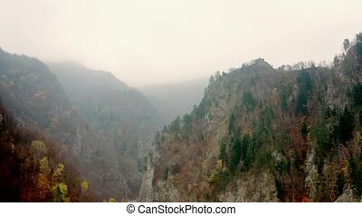 Landscape of misty mountains with Poenari Castle on top