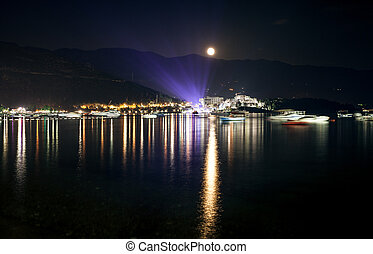 landscape of moon shining over seaside city at dark night -...