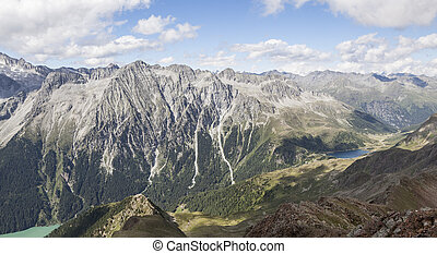 Landscape of mountain peaks, valley and lakes in Alps.