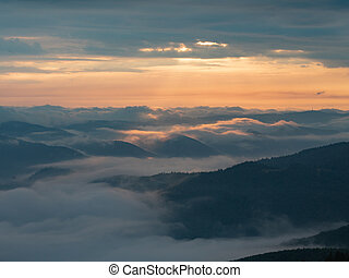 Landscape of mountains, clouds and sun going west....