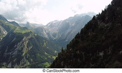 A natural beauty in its full appearance, namely the towering mountains in the French Alps in the warm season when they are covered with greenery