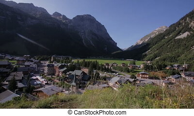 A small countryside in the middle of the mountainous area surrounded by soft, green, grass and trees. The village surrounded by mountains