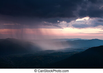 Landscape of rain clouds over the valley between the mountains
