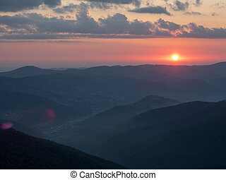 Landscape of red sunset in mountains. The sun illuminating...