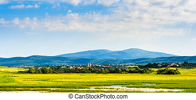 landscape of small town near the lake and mountain -...