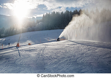 snow cannons working on ski slope in Alps at sunny day -...
