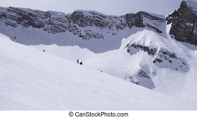 Landscape of snowy mountains in sunny day. Ski resort. Snowboarders on slope.