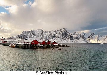 Landscape of the Lofoten Islands in Norway with traditional wooden red fisherman huts in front of the sea and this beautiful mountain in the background. Winter travel destination.