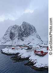 Landscape of the Lofoten Islands in Norway with traditional wooden red fisherman huts in front of the sea and this beautiful moutain in the background. Winter travel destination.
