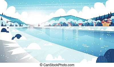 Landscape Of Winter Village Houses Near Mountain Hills And Frozen River Or Lake