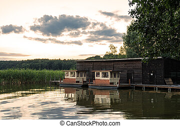 Landscape on a lake with trees and reeds and boatshouse