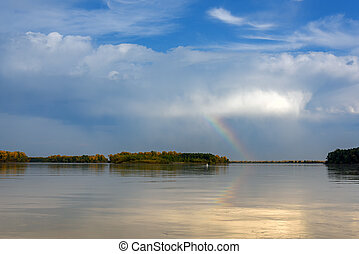Landscape on the river with a rainbow in the sky