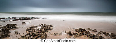 Landscape panorama long exposure image of rocks and sandy beach