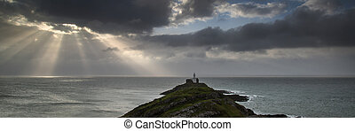Landscape panorama of Mumbles lighthouse in Wales with sunbeams