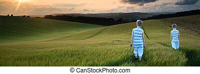 Landscape panorama young boys walking through crop field at sunset