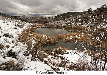 Landscape picture of a reservoir in the desert with snow and clouds