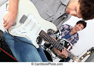 Landscape picture of guys with guitars and drums