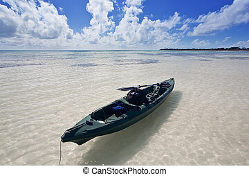 A small canoe drifting in the water under a fantastic sky. Beautiful white sands beach at Bahia Honda State Park in Florida.