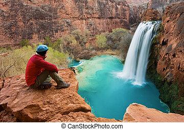 Woman sitting at the edge of a cliff watching Havasu Falls drop into it's turquoise pool. Havasu Canyon, Arizona. Havsupai Reservation.